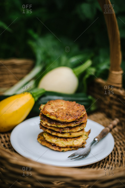 Zucchini fritters on a plate by gourds