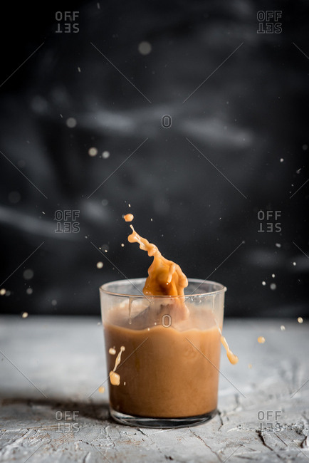 Glass cup with coffee splashing out of it