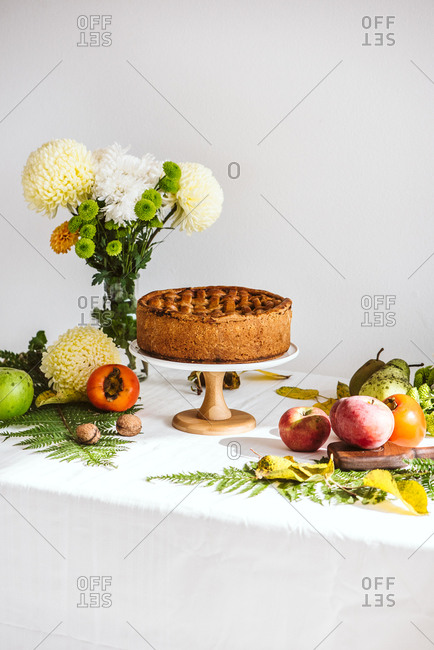 Cake stand with a fresh baked cake on table with fruit