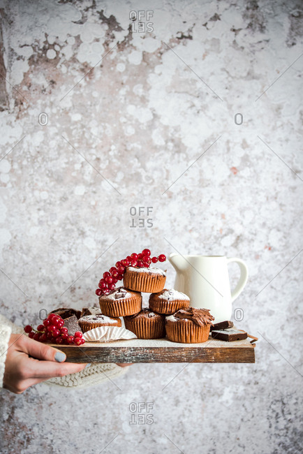 Woman holding wooden board with red berries and fresh baked muffins