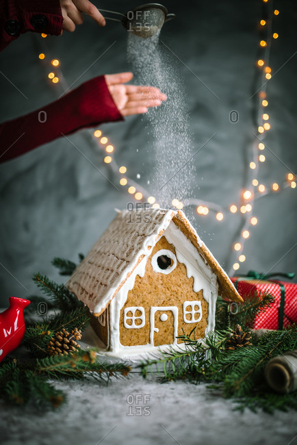 Woman sprinkling powdered sugar over a gingerbread house