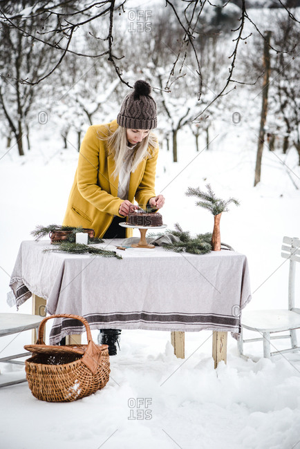 Woman placing branches an chocolate cake in outdoor winter scene