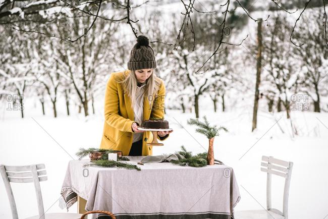 Baker preparing a chocolate cake in outdoor winter scene