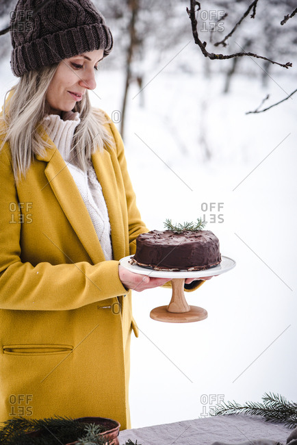Baker holding a chocolate cake in outdoor winter scene