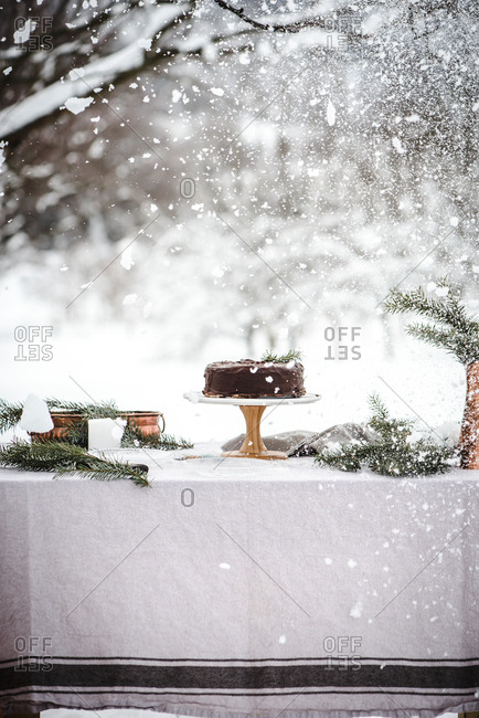 Snow falling over chocolate cake in outdoor winter scene
