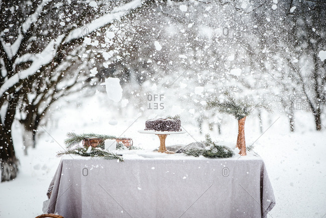 Heavy snow falling over chocolate cake in outdoor winter scene