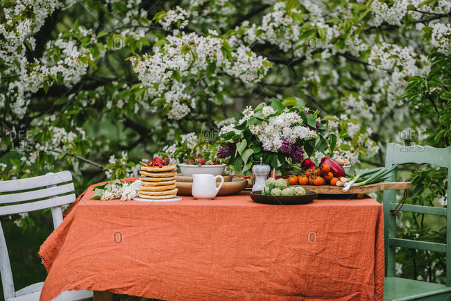 Outdoor breakfast table setting with stack of pancakes and lilacs