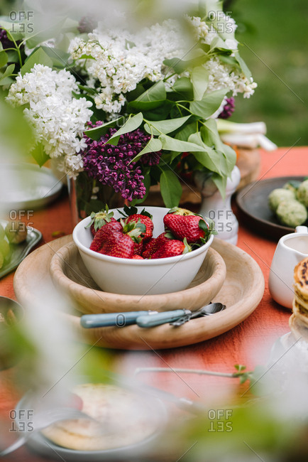 Bowl of strawberries and lilacs on outdoor table