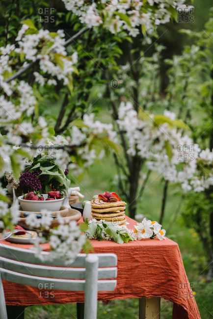 An outdoor breakfast table setting with stack of pancakes and lilacs