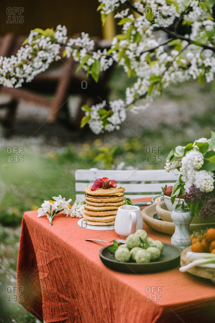 An outdoor table setting with fruit, pancakes and lilacs