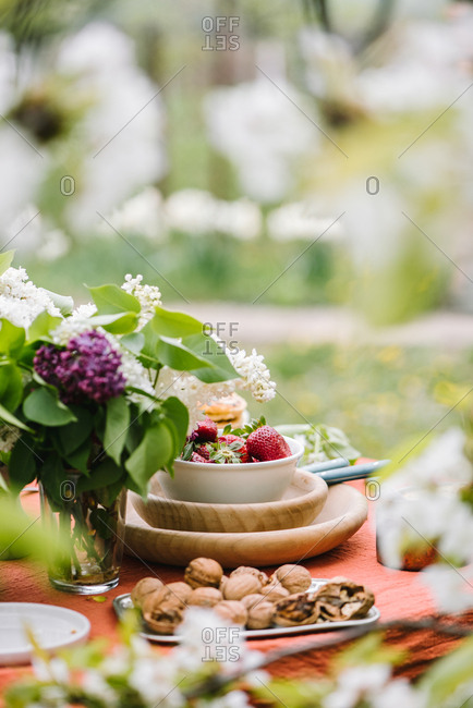 Bowl of strawberries, nuts, and lilacs on outdoor table