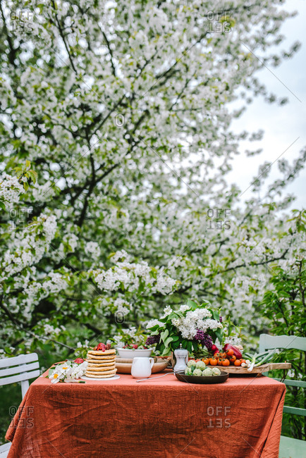 Breakfast table setting with stack of pancakes and lilacs outdoors