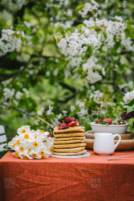 Stack of pancakes with fruit and nuts by daffodils on outdoor table