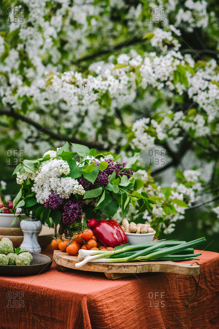 Freshly harvested vegetables on an outdoor table with lilacs