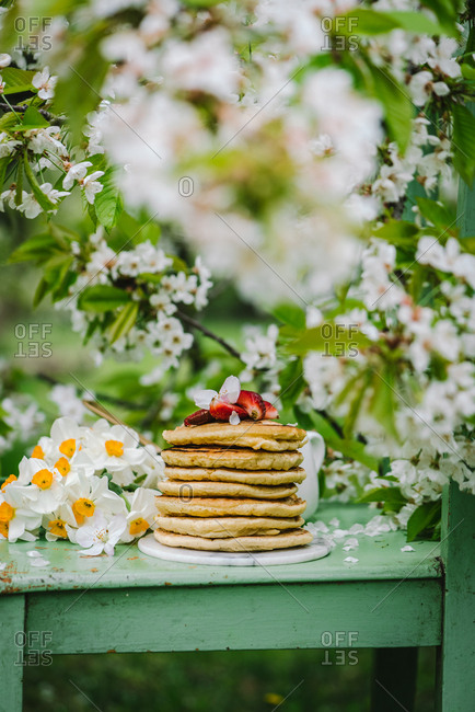 Stack of pancakes on a green chair outdoors with daffodils