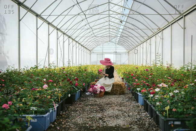 Lady wearing pink hat sitting on a bale of hay and looking at flowers in a greenhouse