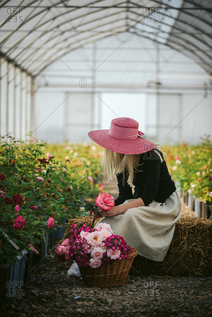 Woman in a pink hat on a bale of hay looking at flowers