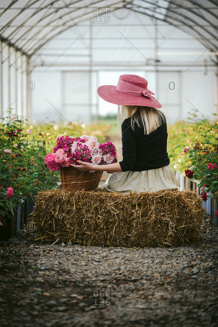 Rear view of a woman in a pink hat by a basket of flowers on a bale of hay in a green house