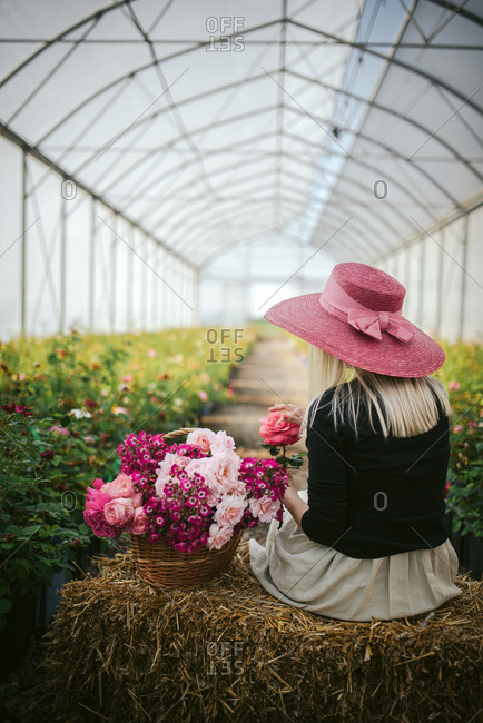 Woman in a pink hat by a basket of flowers on a bale of hay in a green house