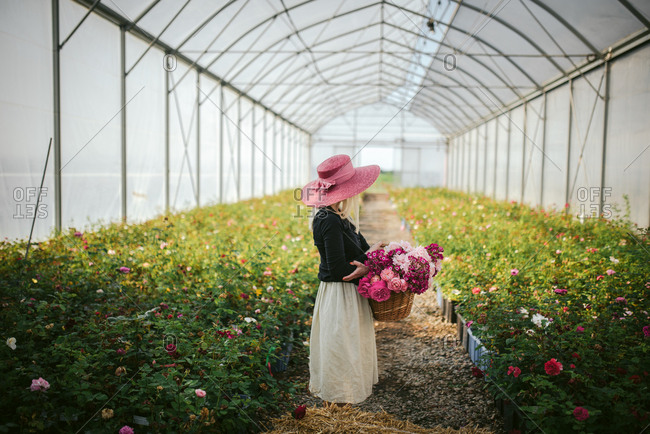 Woman in a pink hat holding a basket of flowers in a greenhouse