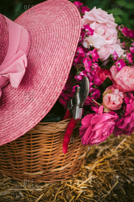 Pink hat on a basket of fresh picked flowers