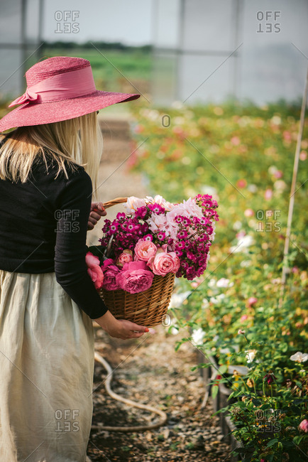 Woman in a pink hat holding a basket of fresh picked flowers in a greenhouse