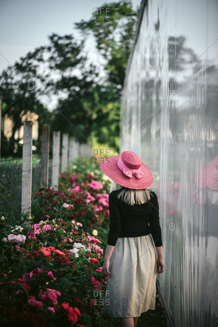 Woman wearing a pink walking by flower bushes outside of a greenhouse
