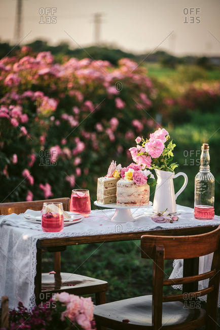 Pink wine and cake on an outdoor table in a flower garden
