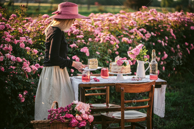 Blonde woman serving cake and wine on an outdoor table in a flower garden