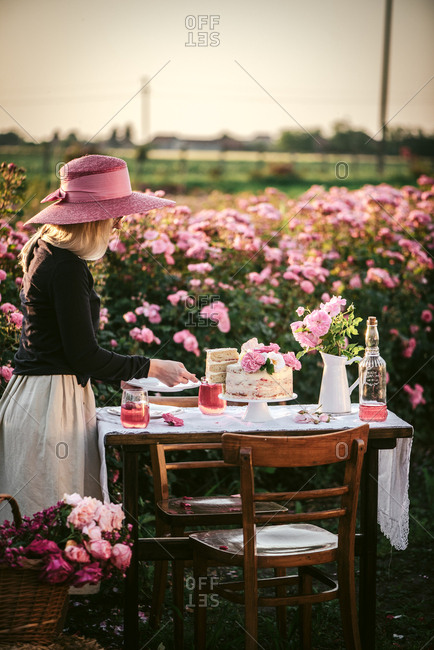 Woman in a pink hat serving cake and wine on an outdoor table in a flower garden