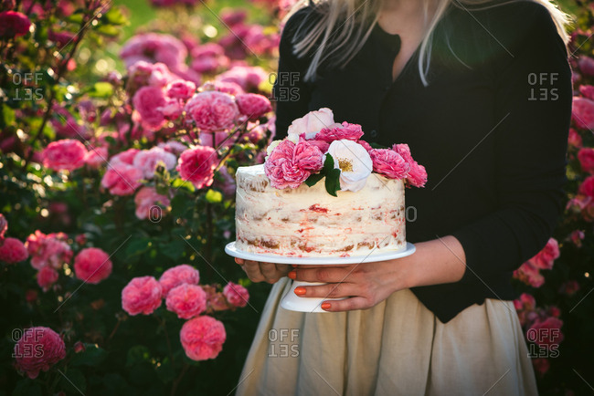 Woman holding a cake topped with flowers in a garden