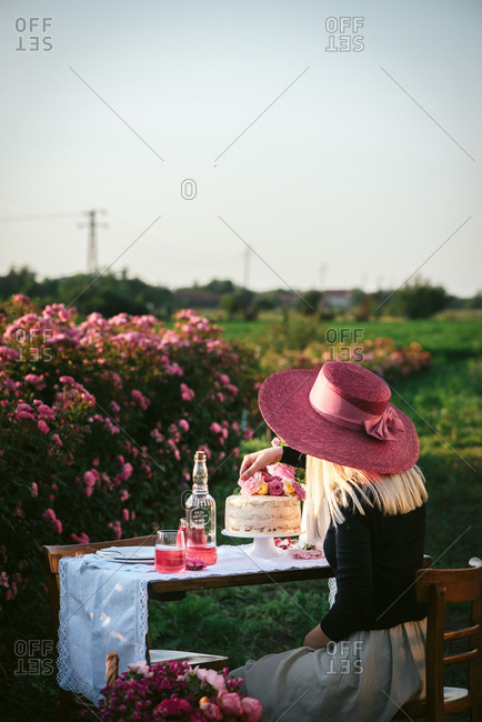 Woman in a pink hat placing flowers on cake on an outdoor table in a flower garden