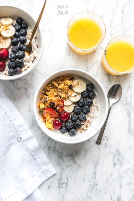Overhead view of a bowl of oats and fruit with orange juice