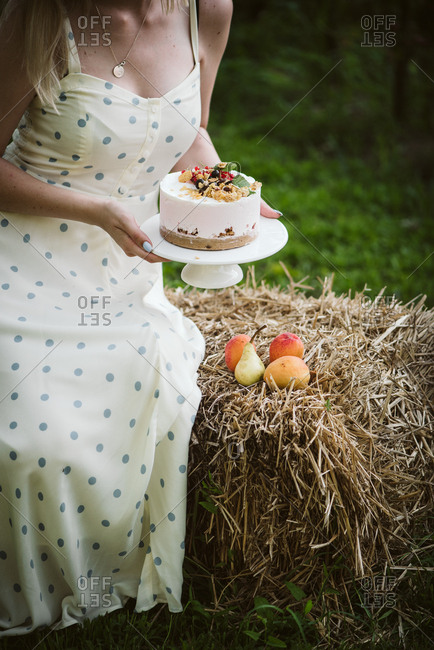 Blonde woman sitting on hay bale with cake
