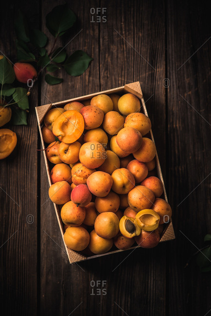 Stone fruit in a box on a wooden surface
