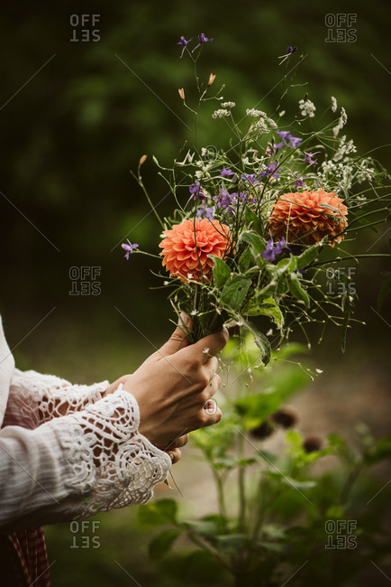 Woman holding fresh picked flowers outdoors