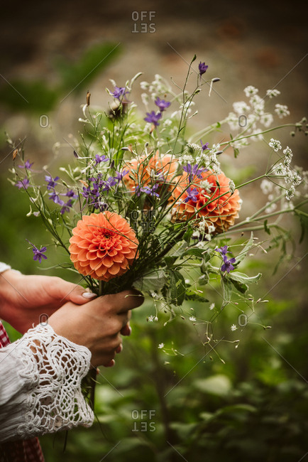Woman's hands holding fresh picked flowers outdoors