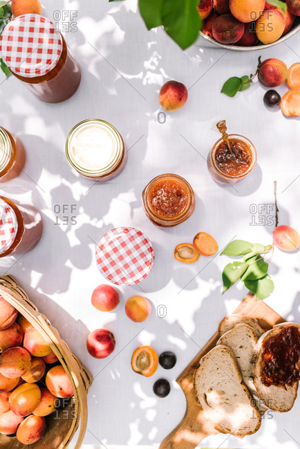 Top view of homemade nectarine jam with toast on a picnic table