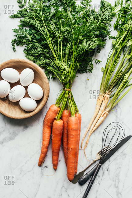 Bunch of fresh picked carrots and eggs on white marbled surface