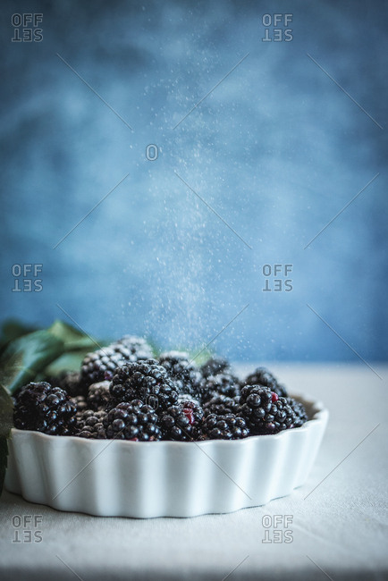 Powdered sugar being sprinkled on dish with blackberries