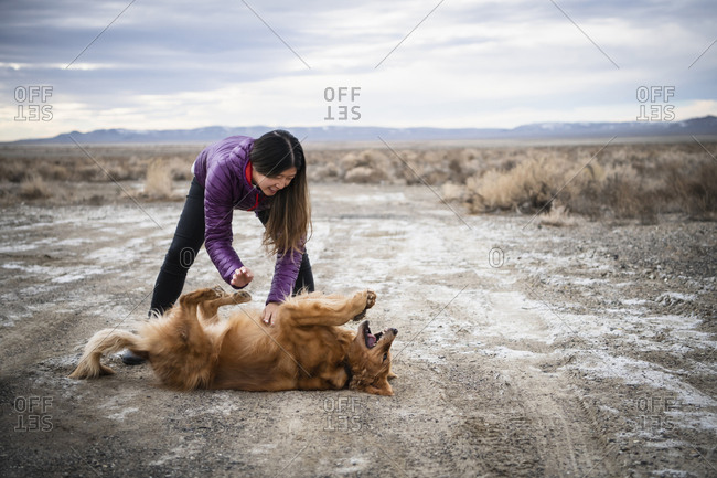 Woman playing with dog on snow covered landscape against cloudy sky