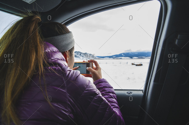 Woman photographing landscape on mobile phone through car window