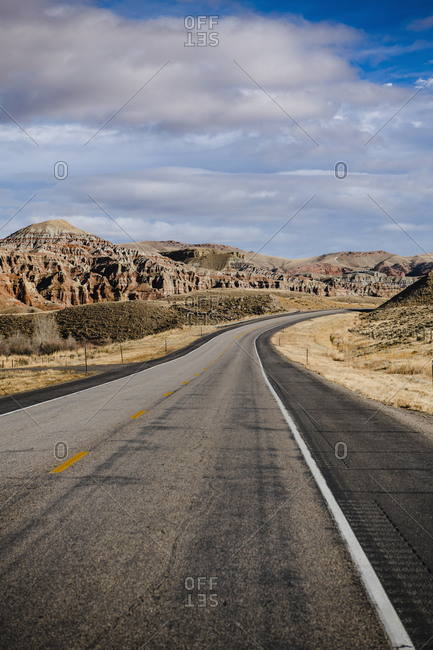 View of empty road amidst rocky mountains against sky