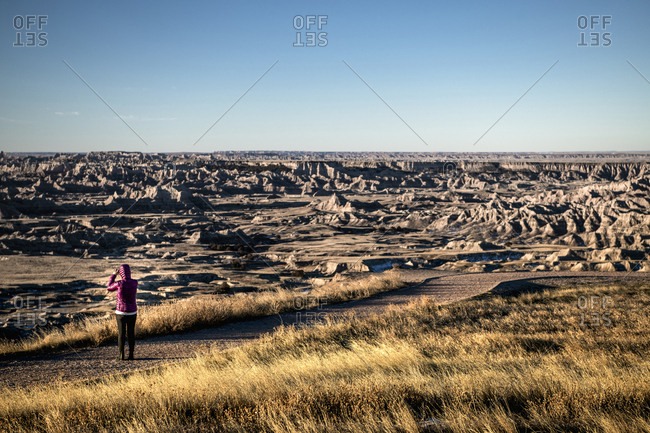 Woman photographing scenic rocky landscape through mobile phone