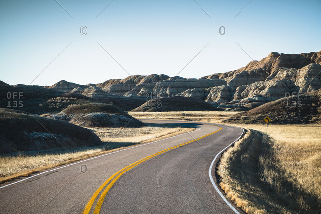 Empty road amidst rock formations against sky