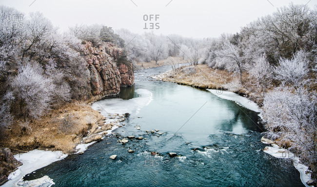 Scenic view of frozen river amidst bare trees during winter