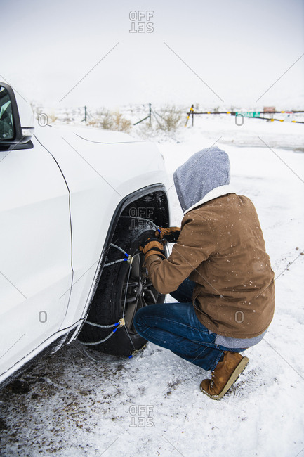 Man tying chain on car tire over snowy landscape