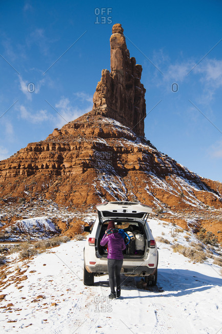 Woman loading car trunk at Valley of Gods during winter