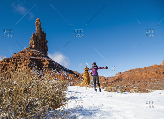 Woman jumping with dog at Valley of Gods during winter