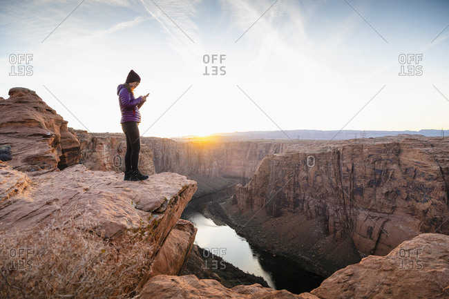 Woman using smart phone while standing on cliff by dam